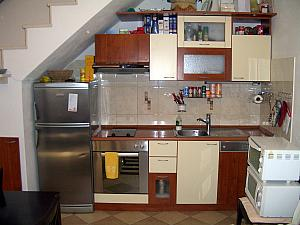 And here's our kitchen, tucked underneath the steps. We didn't have a good place for our microwave or toaster oven, so their stacked on top of one of our dining room chairs.