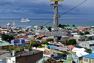 Punta Arenas, Chile, on a hillside at the edge of town. Our ship in the background; signs pointing the location and  distance to faraway cities in the foreground.