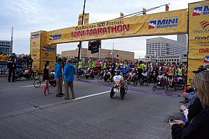 Wheelchair racers lead the pack to start the half marathon. The wheelchair racers finish faster than the runners -- the winner finishes in under an hour!