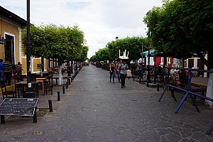 Main tourist street in Granada; worker carrying a table on his head