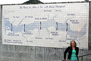 Back in Regua, Kyleen posing for a photo in front of a map that illustrates the five dams along the Douro River.