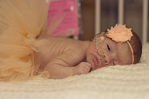 Capri in a tutu and a headband. It doesn't get much cuter than this! She makes her dad's heart melt. (Captured by The Tiny Footprints Project. Thank you!)