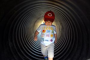 At the pumpkin patch, Cooper walking through a tunnel.