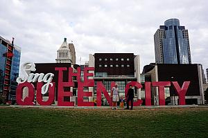 Capri with Grammy and Grandpa at Smale Park downtown - posing at the Sing the Queen City sign.
