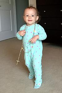 Capri loves to raid Mom's jewelry armoire -- here she is modeling a rosary.