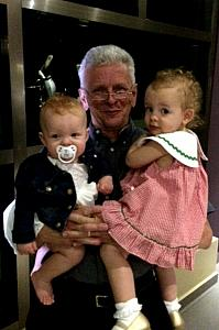 Grandpa at dinner holding his granddaughters!