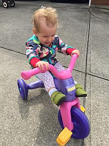 Capri riding on her kids bike