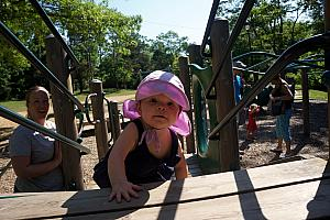 Kenley climbing through a playground