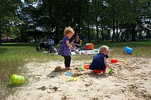 Kenley and Capri playing in the sand while the adults play some volleyball.