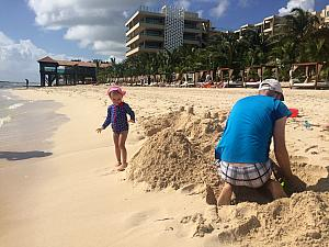 Dad and Capri are building a big sand castle!